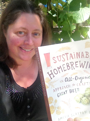 Author Amelia Loftus holding her book Sustainable Home Brewing